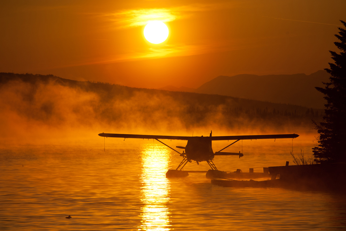 A smoky sunrise silhouettes a float plane at Beluga Lake in Homer, Alaska.